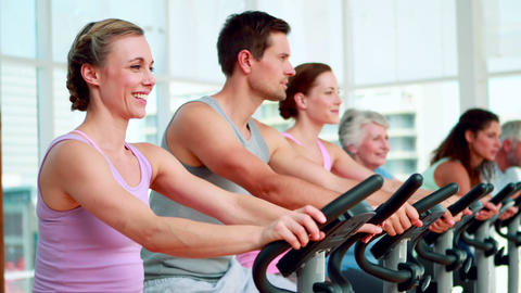 Happy fitness group doing a spinning class Stock Video Footage