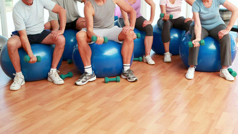 Fitness group sitting on exercise balls lifting hand... Stock Video Footage