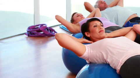 Exercise class doing sit ups on exercise balls Stock Video Footage