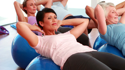 Exercise Class Doing Sit Ups On Exercise Balls stock footage
