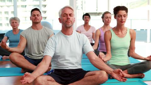 Yoga class sitting in lotus position together Stock Video Footage