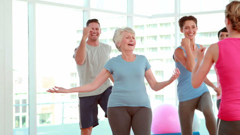Aerobics class stepping and laughing together Stock Video Footage
