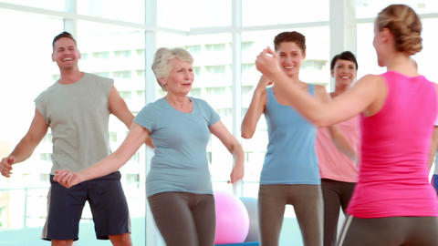 Aerobics class stepping and laughing together Footage