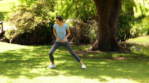 Fit girl stopping to stretch her legs on a jog Stock Video Footage