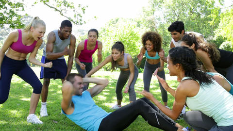 Fitness group cheering on man doing sit ups Stock Video Footage