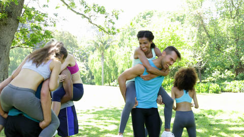 Fit group of friends having fun and messing in the park Stock Video Footage