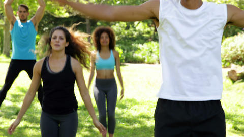 Fitness class doing star jumps in the class Stock Video Footage