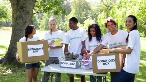 Group of young volunteers sorting donation boxes Footage