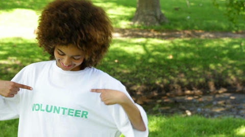 Pretty volunteer smiling at the camera and pointing to tshirt Footage
