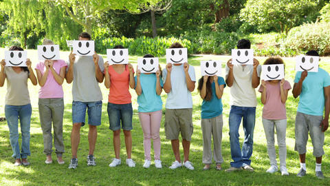 Group of casual young friends holding smiley faces over their faces Footage