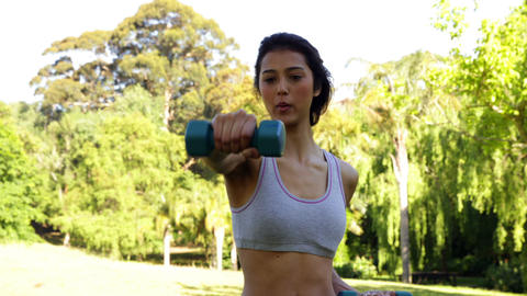 Smiling fit brunette lifting dumbbells in the park Stock Video Footage