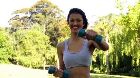 Smiling fit brunette lifting dumbbells in the park Footage