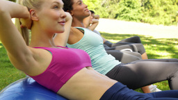 Fitness group doing sit ups on exercise balls Stock Video Footage