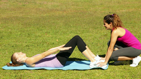 Woman doing sit ups in the park with her trainer Stock Video Footage