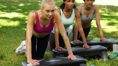 Fitness class doing press ups on steps together Stock Video Footage