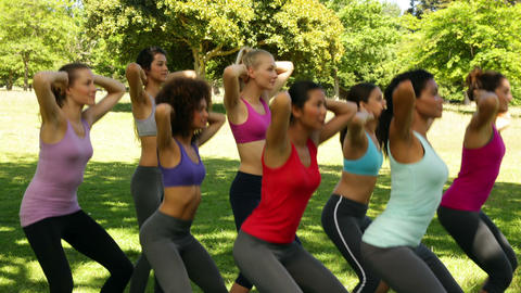 Fitness class doing squat sequence together Stock Video Footage