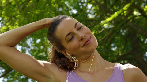 Runner stretching neck listening to music in the park Stock Video Footage