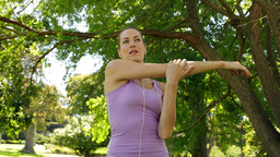 Runner stretching arms listening to music in the park Stock Video Footage