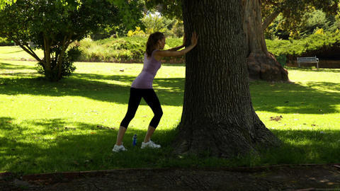 Runner stretching her legs leaning against tree Footage