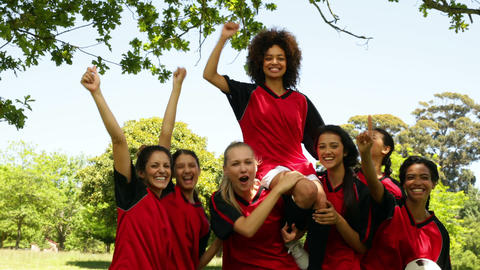 Female football team celebrating a win in the park Stock Video Footage