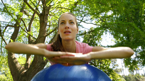 Fit woman doing core exercises on exercise ball in the park Live Action