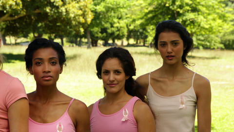 Diverse women wearing pink for breast cancer awareness in the park Footage