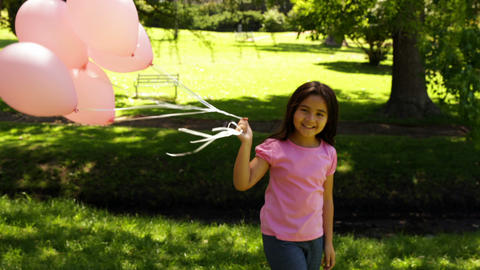 Little girl carrying balloons for breast cancer awareness in the park Footage