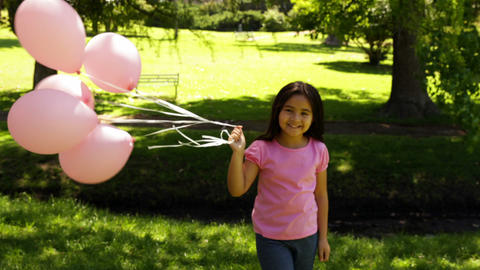 Little girl carrying balloons for breast cancer awareness... Stock Video Footage