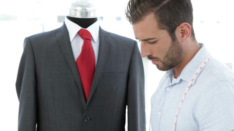 Handsome tailor using tablet beside suit on mannequin Footage