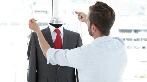Handsome tailor measuring suit on mannequin Stock Video Footage