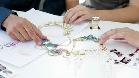 Design team looking at costume jewelry and talking Footage