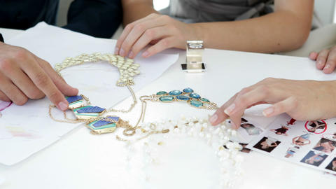 Design team looking at costume jewelry and talking Stock Video Footage
