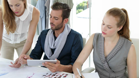 Fashion design team working together at table with tablet pc Stock Video Footage