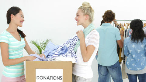 Team of people going through donation box of clothes Stock Video Footage
