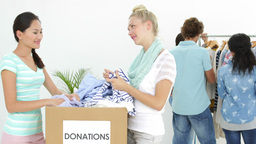 Team of people going through donation box of clothes Footage