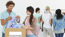 Team of happy people going through donation box of clothes Stock Video Footage