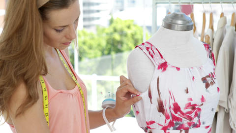 Smiling fashion designer looking at camera adjusting dress on mannequin Footage