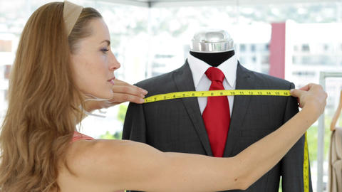 Pretty fashion designer measuring suit on mannequin Footage