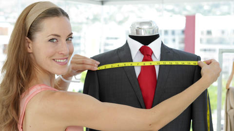 Pretty fashion designer measuring suit on mannequin Stock Video Footage