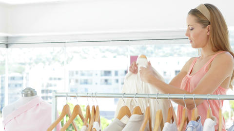 Attractive fashion designer looking through her clothing... Stock Video Footage