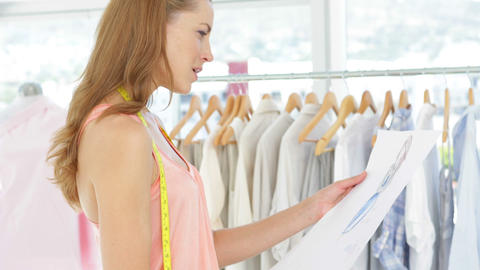 Attractive fashion designer looking at sketch Stock Video Footage