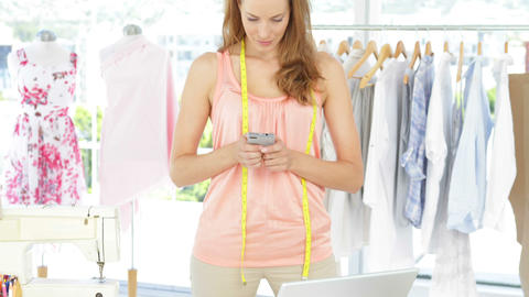 Attractive fashion designer texting on the phone Stock Video Footage