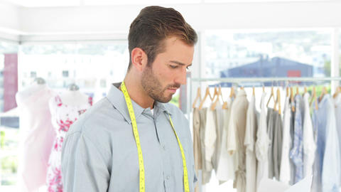 Handsome fashion designer looking at sketches Stock Video Footage