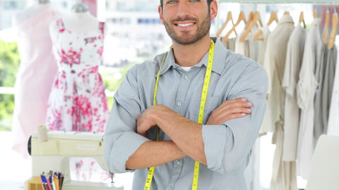 Handsome fashion designer smiling at camera with arms crossed Footage
