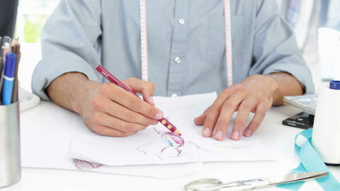 Handsome fashion designer sketching at his desk Stock Video Footage