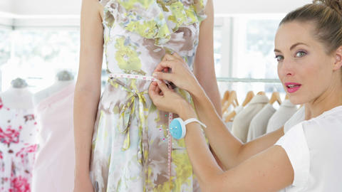 Pretty fashion designer measuring waist of dress on a model Footage