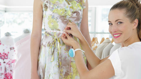 Pretty fashion designer measuring waist of dress on a model Stock Video Footage