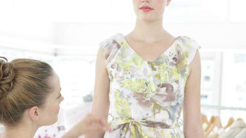 Pretty fashion designer measuring dress on a model Stock Video Footage