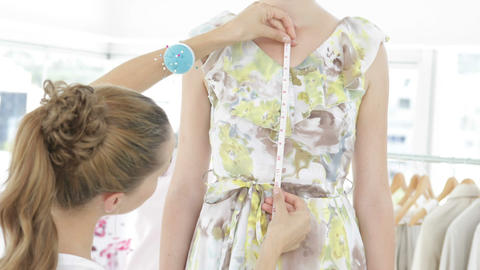 Pretty fashion designer measuring dress on a model Footage
