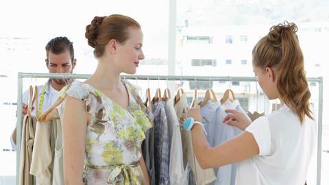 Fashion designer showing a dress to a model Stock Video Footage